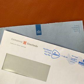 Blauwe envelop Belastingdienst en witte envelop gemeente Enschede